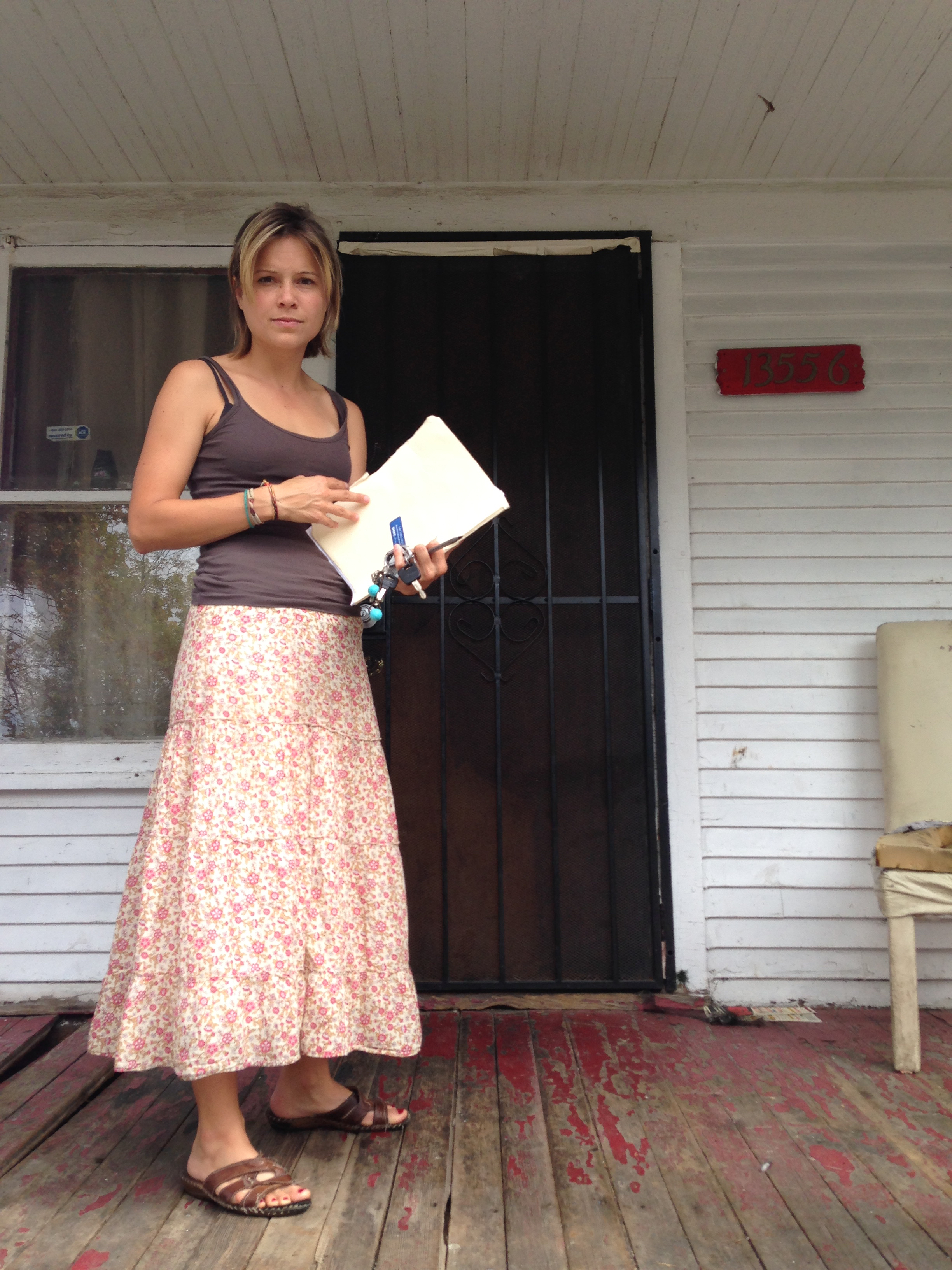 A portrait of Michele in front of a house in Detroit